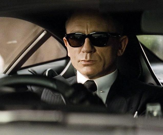 Daniel Craig as James Bond, wearing Tom Ford Snowdon sunglasses in SPECTRE, while driving his Aston Martin DB10.