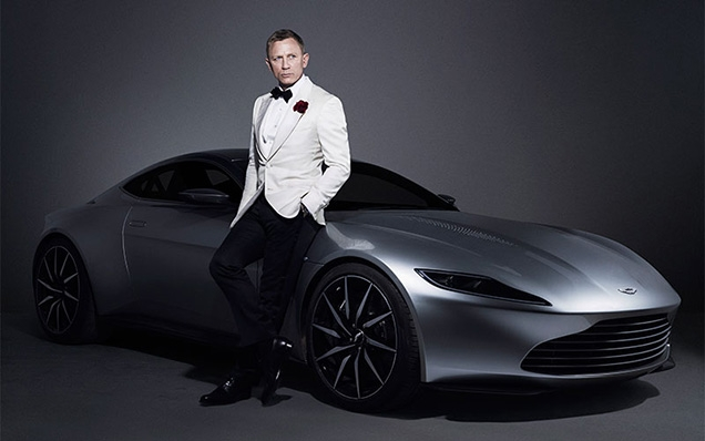 Daniel Craig as James Bond poses with the Aston Martin DB10