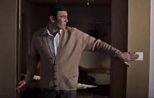 George Lazenby as James Bond wearing a light brown cardigan with two front pockets in On Her Majesty's Secret Service