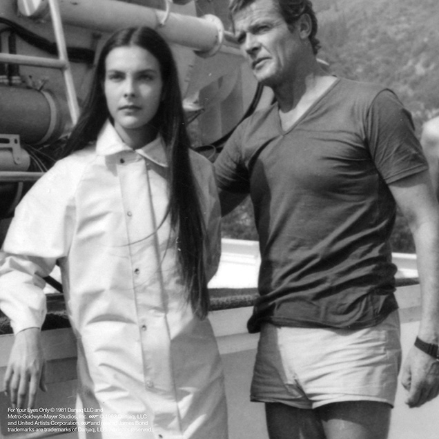 Roger Moore in a behind the scenes photo of For Your Eyes Only wearing a blue v-neck t-shirt and white shorts. The shorts are not seen in the film, he wears long trousers instead.