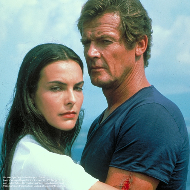 Roger Moore as James Bond in For Your Eyes Only wearing a blue v-neck t-shirt and white shorts, just before he and Melina Havelock are thrown int the sea