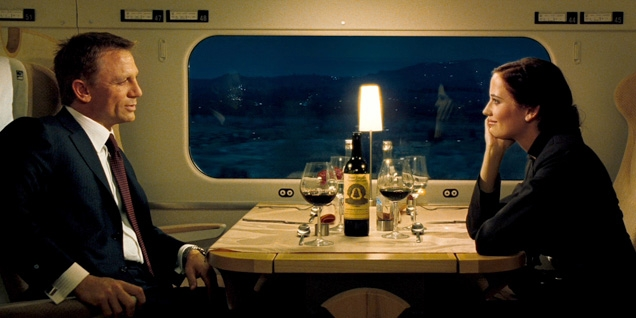 James Bond (Daniel Craig) and Vesper (Eva Green) in the train's dining car, drinking a bottle of Château Angélus