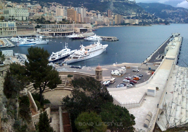 The theatre is visible in the left front of the image and the the harbor of Monaco behind it
