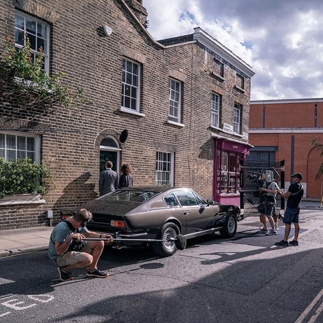 James Bond and Moneypenny and the Aston Martin V8 on the streets of London during filming of No Time To Die.